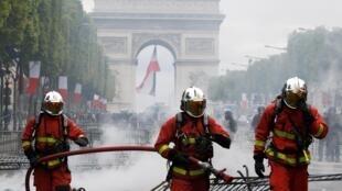 Des pompiers sur les Champs-Élysées éteignent un incendie, après le défilé du 14-Juillet à Paris, en 2019. (Image d'illustration)
