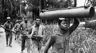 Le bazooka sur la tête, un rebelle biafrais marche à travers la brousse. Photo prise le 31 juillet 1968.