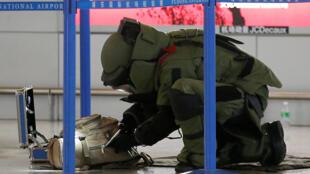 Um especialista em desarmamento de bombas verifica uma bagagem perto do local de uma explosão em um terminal no aeroporto de Xangai Pudong International, China, 12 de junho de 2016.