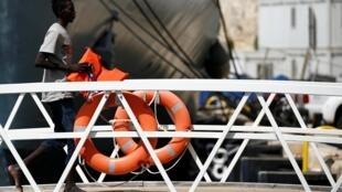 Migrante anda em navio de resgate das Forças Armadas maltesas, que salvaram 50 náufragos neste domingo (7).