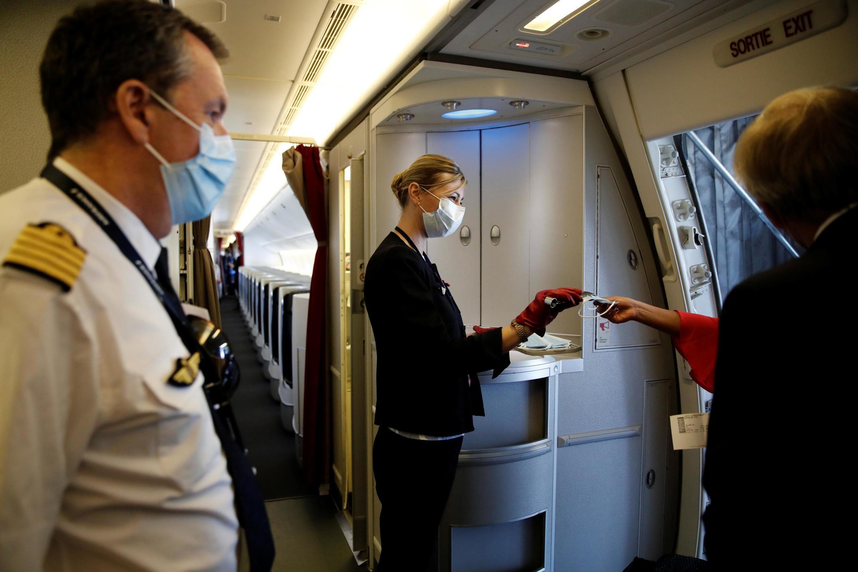 Membros da tripulação da Air France a distribuir máscaras aos passageiros no aeroporto de Paris-Charles de Gaulle, 6 de maio de 2020. Até segunda-feira, 11 de Maio.
