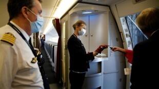 Los miembros de la tripulación de Air France distribuyen mascarillas a los pasajeros en el aeropuerto de Paris-Charles de Gaulle el 6 de mayo de 2020. A partir del lunes 11 de mayo, la temperatura de los pasajeros será controlada.