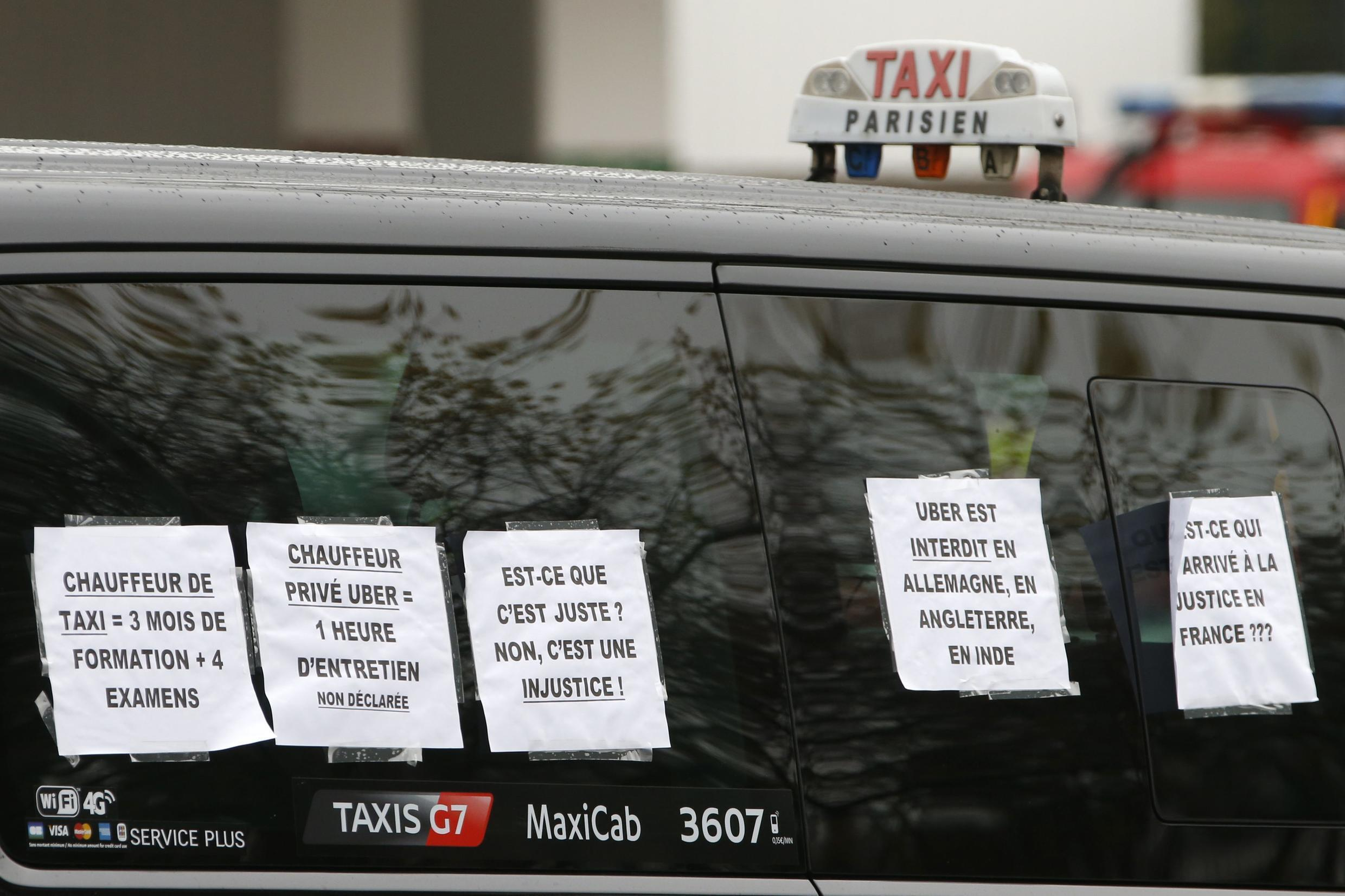 A striking Paris taxi takes part in a demonstration over the Paris ring road December 15, 2014. The UberPop transport service will be forbidden in France beginning January 1, 2015, the French interior ministry said on Monday