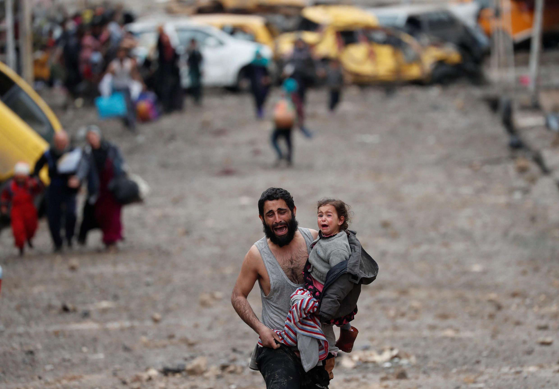 Un hombre grita mientras huye con su hija de la parte controlada por el grupo Estado Islámico, la foto fue tomada el 4 de marzo 2017 durante una de las batallas en el oeste de Mosul.