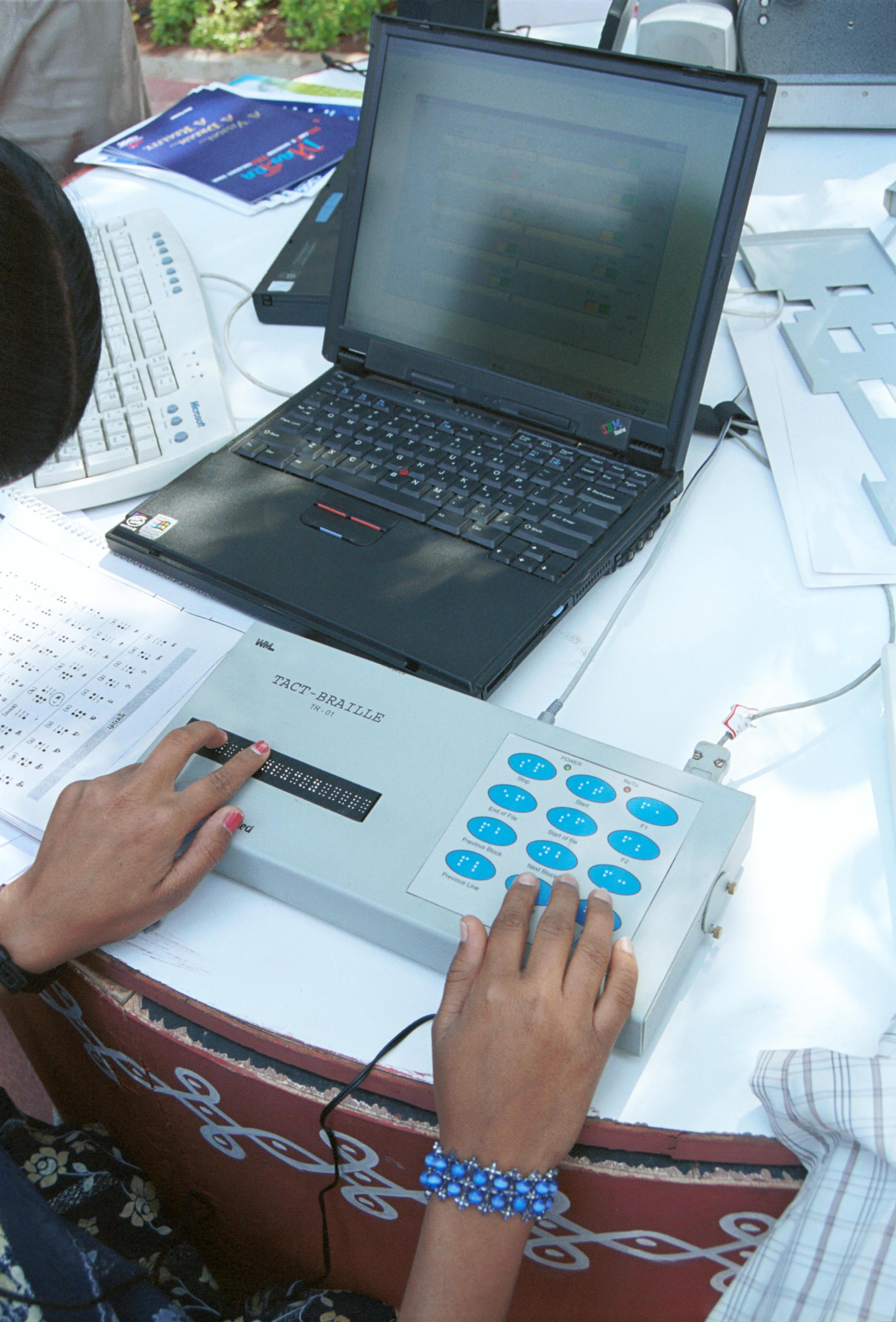 Pessoa cega usando braille para navegar na internet.