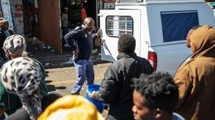 A member of the South African Police Service reaches for his gun in front of a looted shop during a riot in the Johannesburg suburb of Turffontein on September 2, 2019 as protesters loot alleged foreign-owned shops in a wave of violence targets foreigers.