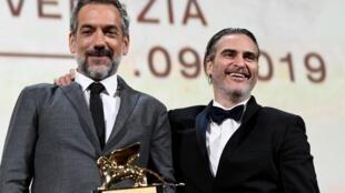 Đạo diễn Todd Phillips (trái) hãnh diện với giải Sư tử vàng Liên hoan phim Venise 2019.