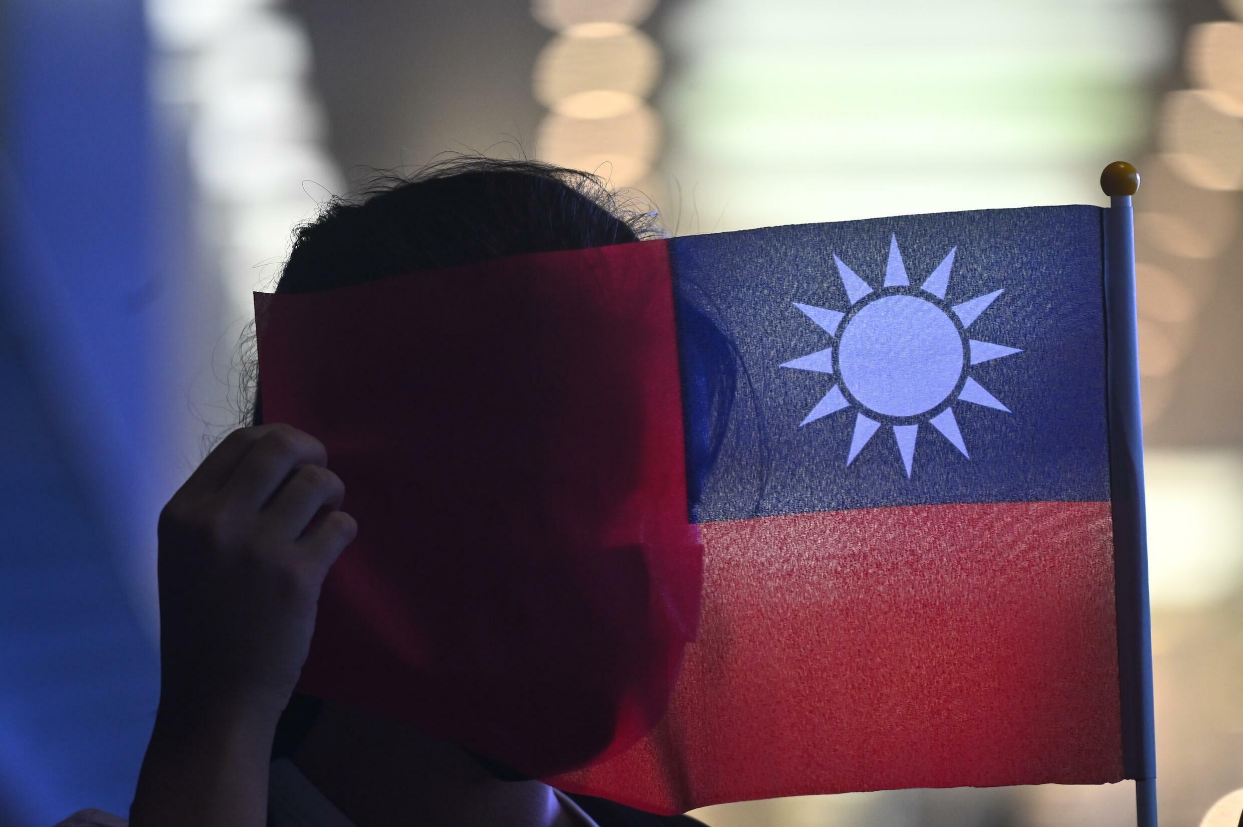 A woman holds a Taiwanese flag to mark the island's National Day. Beijing claims Taiwan as its own and has vowed to one day retake it -- by force if needed