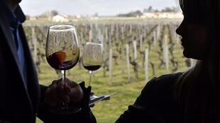 In this file photo taken on April 10, 2018 visitors taste red wine during a wine tasting session at the Chateau La Dominique in Saint-Emilion, southwestern France, during the 'Semaine des Primeurs' to present wines from the Bordeaux region.
