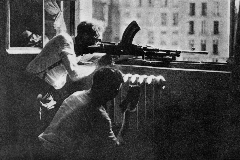 Des Parisiens tirent sur les troupes allemandes depuis une fenêtre de la préfecture de police de Paris, en août 1944.