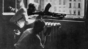 Des Parisiens tirent sur les troupes allemandes, depuis une fenêtre de la préfecture de police de Paris durant la libération de Paris, en août 1944.