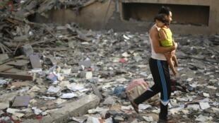 Palestino caminha com criança entre escombros de prédios destruídos.