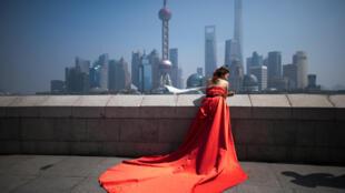Une femme pose pour une photo de mariage devant le quartier financier de Pudong à Shanghai, le 19 mars 2015.