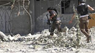Rebeldes sírios entre escombros em al-Asali, no distrito de Damasco, em 22 de junho de 2013.