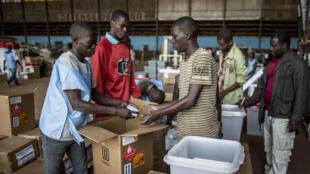 Les agents de la commission électorale préparent le matériel électoral qui doit être livré pour le référendum, dans un hangar de l'aéroport de Bangui, le 11 décembre 2015.