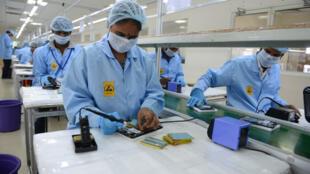 Des techniciens, dont une femme au premier plan, travaillent sur des circuits intégrés pour le compte de l'entreprise canadienne DataWing à Hyderabad, en Inde. (photo d'illustration)