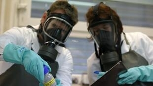 Funcionários de laboratório de testes da OPAC examinam substância similar ao gás Sarin, arma química utilizada no conflito sírio.