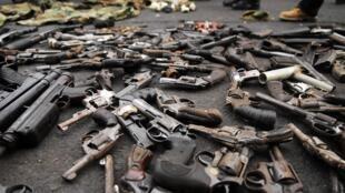Des armes étalées sur le sol, lors d'une opération de désarmement de gangs au Salvador.