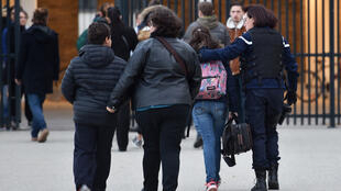 Pupils with a parent and a gendarme arrive at the victims' school in Millas, near Perpignan, on Friday