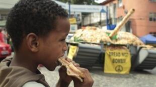 Garoto come sanduíche em frente à tanque do exército recoberto de pão, simbolizando a ausência de violência na favela de Santa Marta, Rio de Janeiro, pacificada pelas UPPs.