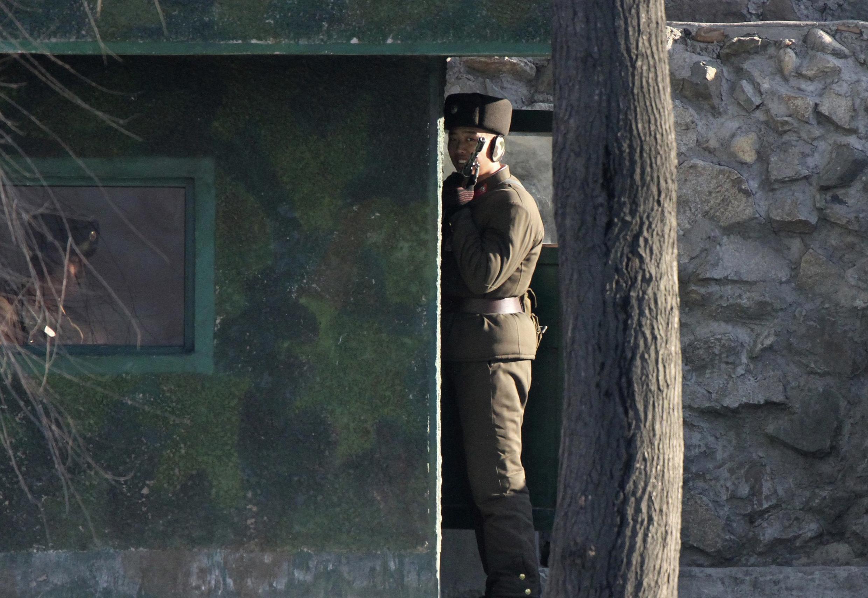 2013年12月21日,中朝边境鸭绿江对岸的朝鲜士兵正在持枪执勤
