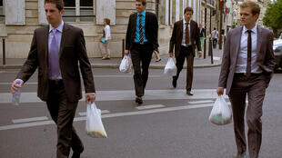 French workers walk in the streets of Paris during their lunch break.