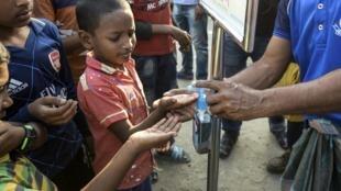 Des enfants bangladais reçoivent du désinfectant pour les mains pour lutter contre la propagaiton du Covid-19, dans un bidonville de Dhaka, le 19 mars 2020.