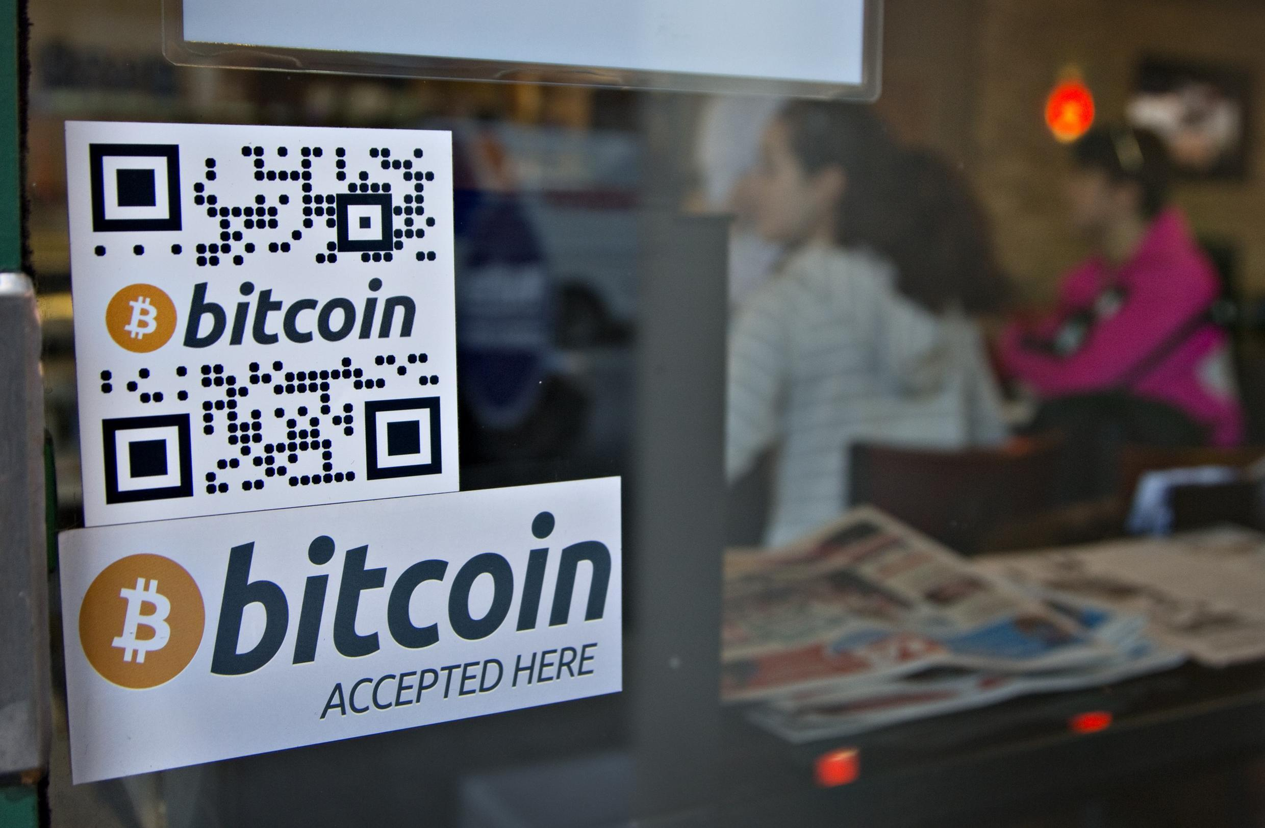 Signs on window advertise a bitcoin ATM machine that has been installed in a Waves Coffee House in Vancouver