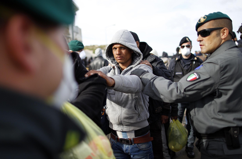 Тунисские беженцы под эскортом итальянской полиции на острове Лампедуза