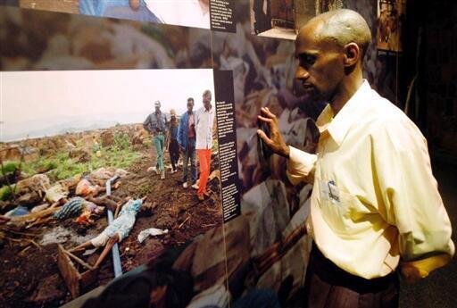 Un survivant du génocide et guide du mémorial regarde un panneau de photos du génocide, à Kigali.