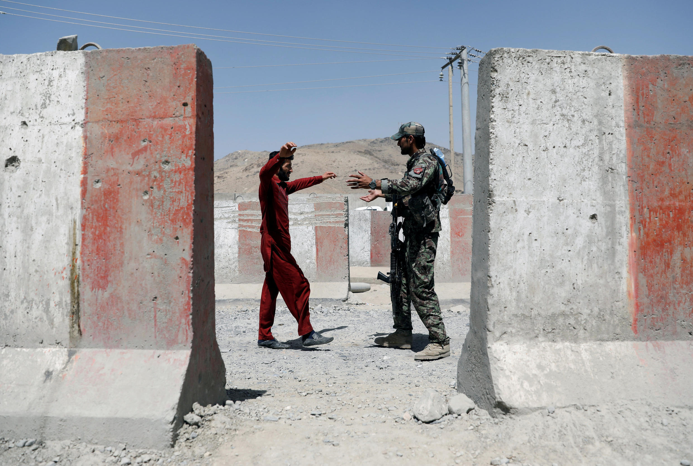 غزنی: یک سرباز فرد مظنونی را تفتیش میکند