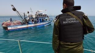 Un membre de la garde nationale tunisienne contrôle un bateau de pêcheur au large des côtes tunisiennes (image d'illustration).