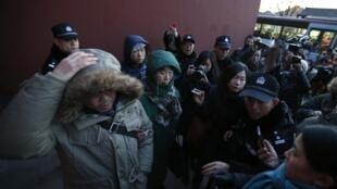 Des familles des victimes chinoises de «l'accident» du vol MH370 de Malaysia Airlines, à Pékin, repoussées par la police alors qu'ils répondent à des interviews, le 30 janvier 2015.