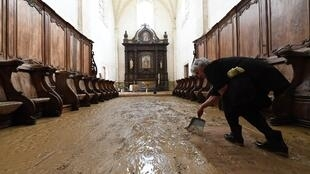 A volunteer cleans up in the Abbey of Chancelade following the flooding