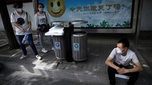 Trois jeunes chinois attendent un bus pour chercher du travail, après avoir perdu leur emploi dû à la crise liée au coronavirus, à Pékin, le 13 mai 2020.