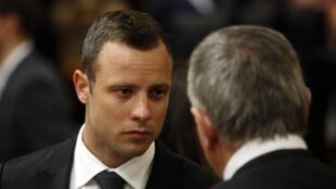 Oscar Pistorius en entretien avec son avocat Barry Roux, le 5 mars 2014 au tribunal de Pretoria.