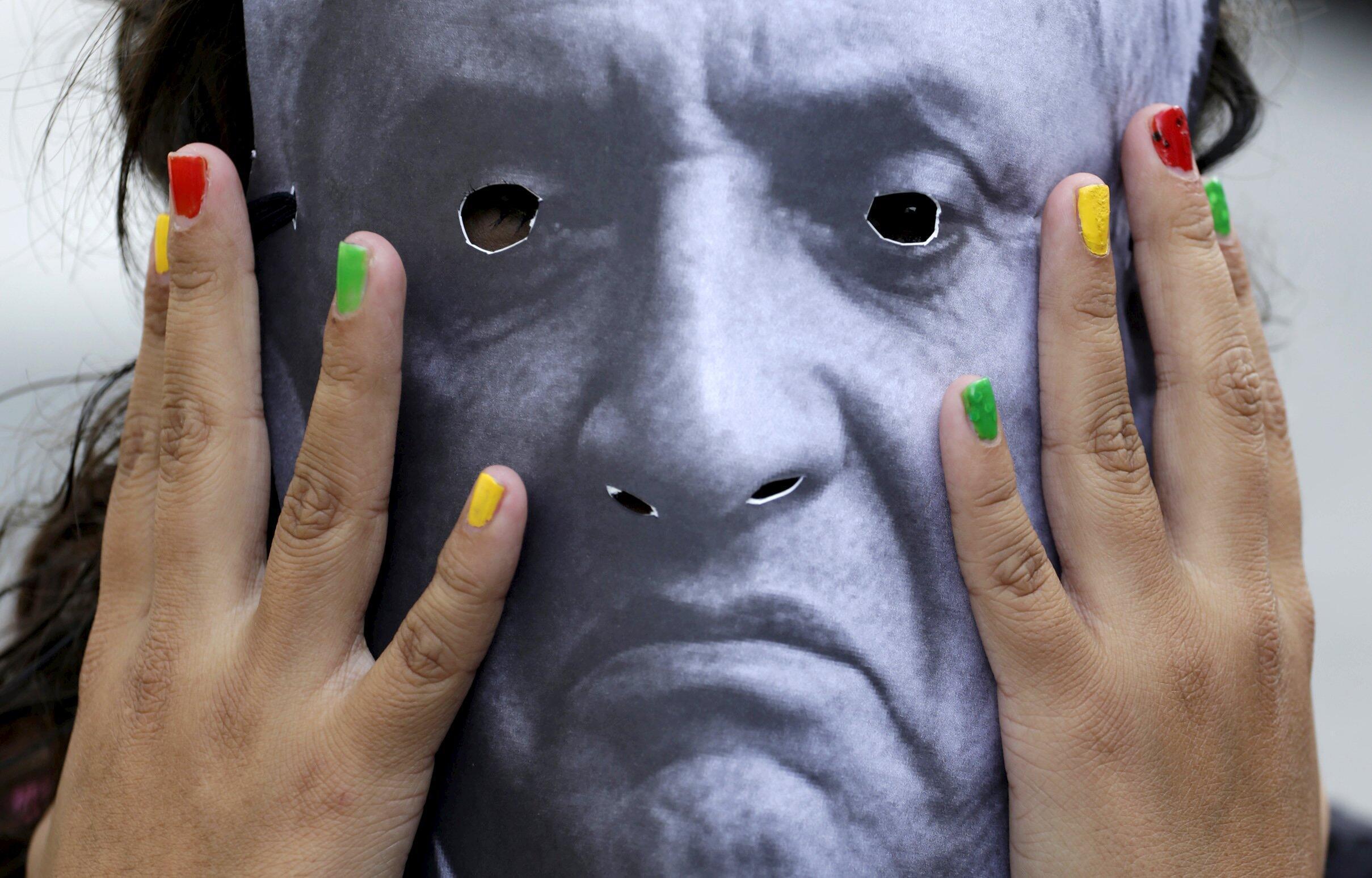 Una mujer lleva una máscara con la cara de Otto Pérez Molina durante una manifestación para pedir su renuncia, el pasado 8 de agosto en la Ciudad de Guatemala.