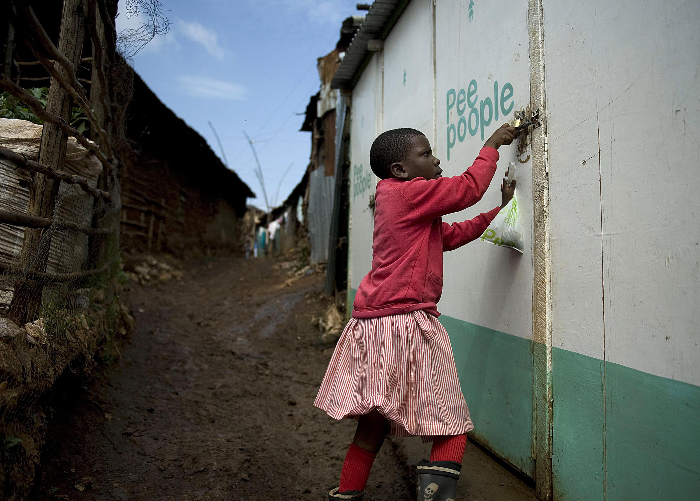 Une petite fille sort des latrines du bidonville de Kibera, à Nairobi, où le manque d'hygiène menace en permanence la santé des habitants.