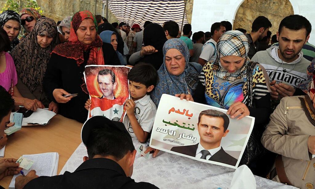 Wananchi wa Syria wakipiga kura wakiwa na picha za rais wao, Bashar al-Assad.