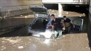 French fireman work near an abandoned car stuck in muddy waters near an underpass after flooding caused by torrential rain in Cannes, France, October 4, 2015.