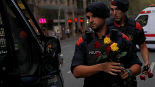 Каталонские полицейские несут цветы, которые им дарили участники марша против террора. 26 августа 2017 года, Барселона.