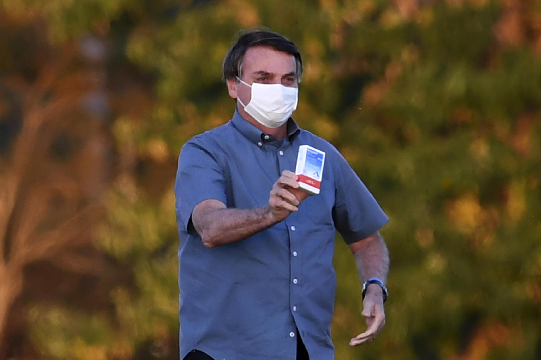 El presidente brasileño Jair Bolsonaro muestra una caja de hidroxicloroquina a sus seguidores fuera del Palacio Alvorada en Brasilia, el 23 de julio de 2020