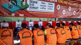 Indonesian inmates at a Jakarta prison talk via video to family members after visits were stopped because of coronavirus fears. Authorities have now gone further, and are releasing tens of thousands of prisoners in a bid to stop the spread of the virus in overcrowded jails
