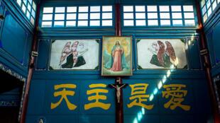 Un portrait de Jésus suspendu au-dessus d'une croix dans une église de la petite ville de Dali, au Yunnan, le 10 décembre 2015. Sur le mur, écrit en chinois : «Dieu est amour».