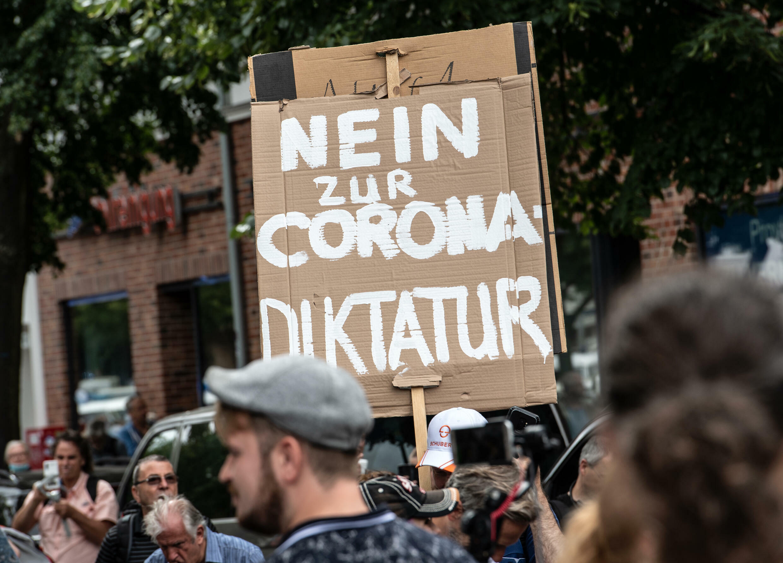 """Manifestantes antirrestricciones marchan en una protesta prohibida en Berlín el 1 de agosto de 2021 con una pancarta que dice """"No a la dictadura del corona"""""""