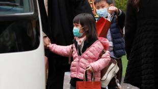 香港流感病死人数达到125人。图为面带口罩的香港儿童做校车回家,2018年2月7日。