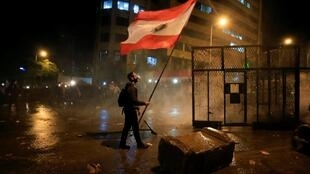 Un manifestant défie les forces de l'ordre devant le siège du gouvernement libanais, à Beyrouth, le 25 janvier 2020.