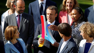 rench President Emmanuel Macron (C) and Laura Flessel (R), Minister of Sport, hold a Paris 2024 Olympics bid logo as Prime Minister Edouard Philippe (L) and ministers look on during a family photo in the gardens of the Elysee Palace