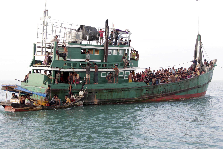 Migrantes rohingya e de Bangladesh em um barco na costa da Sumatra