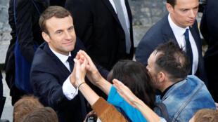 Après la cérémonie officielle à l'Arc de Triomphe, Emmanuel Macron serre les mains de quelques militants d'En marche!.